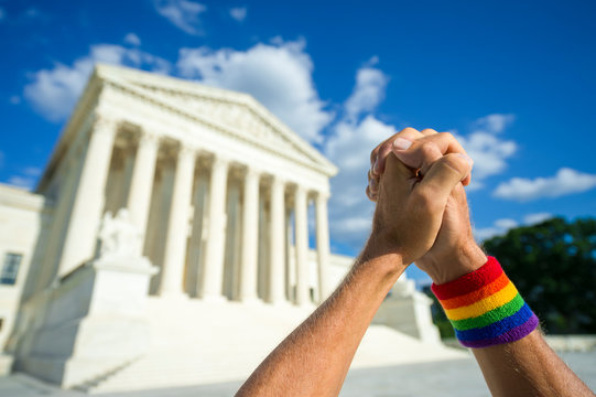 Pleading hands wearing gay pride rainbow flag wristband clasped in prayer outside the Supreme Court building in Washington, DC, USA