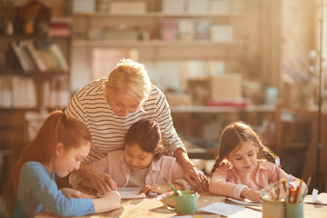 Portrait of mature woman working with group of little girls painting in art class, scene lit by serene sunlight, copy space