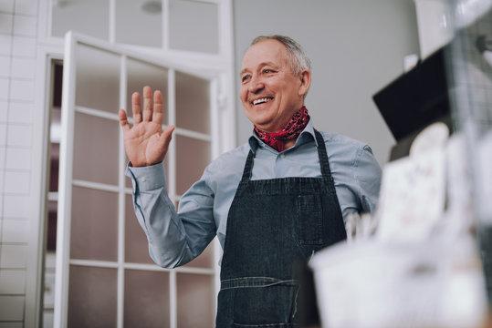 Joyful senior man in apron showing hello gesture