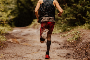 Fototapete - back dirty man runner in compression socks running on spring trail