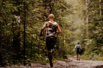 Fototapete - back dirty man runner running on spring trail in forest
