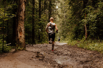 Fototapete - back bald male runner run on dirt trail in forest
