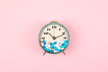 Old alarm clock with Tablets, medicine and pills on clock face on pink background. colorful capsules on  clock. Health care, reform, Take medicine on time concept