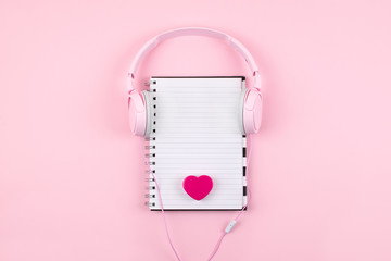 Minimal workplace with white blank notepad, pink headphones, heart on pink background. Top view. Flat lay