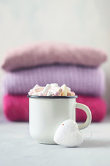 Coffee with marshmallows in white enameled metal cup and white heart on the background of stack of pink knitted sweaters on table
