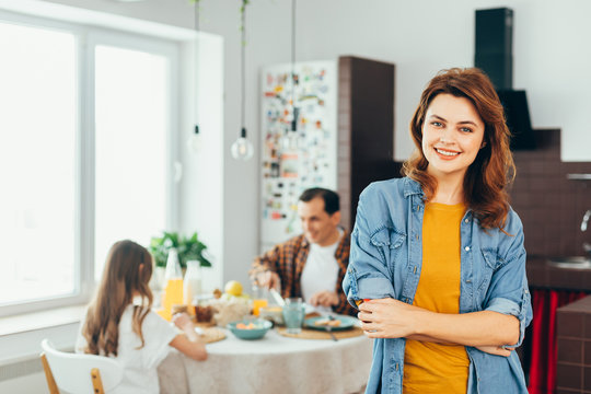 Waist up of cheerful woman and her family on the background