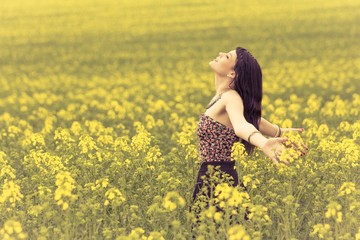 Happy beautiful woman in free summer love of youth wellbeing. Attractive young beauty girl enjoying the warm sunny sun in nature rapeseed field takes time feeling sustainability and contemplation