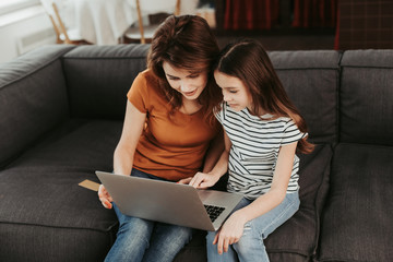Mother and daughter sitting on sofa with laptop