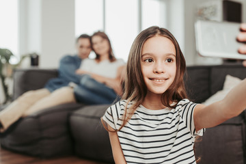 Smiling girl making selfie with parents at home