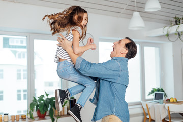 Happy father and daughter playing together at home