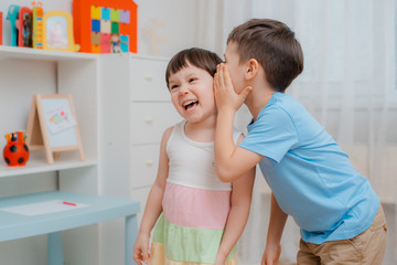 Funny children, brother and sister are friends whisper and laugh. Children's secrets. Little laughing boy and girl.