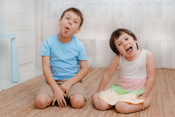 Children, boy girl, naughty floor room They grimace laugh. amusing. Kids bullies Naughty jokers children's fun Restless Child psychology friendship parenting baby 3 years 6 years siblings