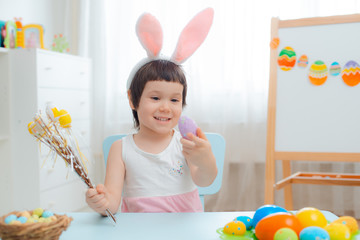 Little girl in bunny ears are playing with Easter eggs. Kids celebrating Easter. Children on Easter egg hunt. Home decoration, pastel bunny banner.