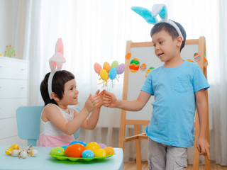 Little boy and girl in bunny ears are playing with Easter eggs. Kids celebrating Easter. Children on Easter egg hunt. Home decoration, pastel bunny banner. brother and sister give a bouquet