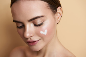Obraz Portrait of peaceful young lady with makeup and heart picture on face - fototapety do salonu