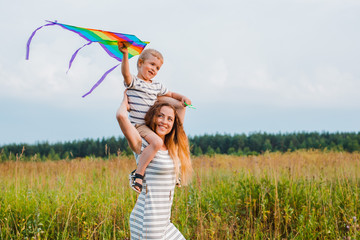 Mom son play actively have fun outdoors Happy motherhood childhood youth Care of children Health education, active rest nature Parent kid having fun lifestyle mothers day setting sun. Kite run grass