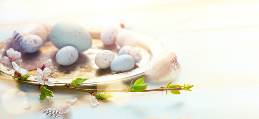 Happy Easter background; Easter Eggs with Spring Flowers on White Wooden Background