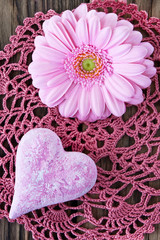 Pink flowers and heart against wooden background