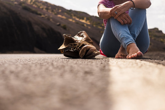 Ground alternative point of view of woman sitting on the road with nude feet and a broken pair of shoes near her - concept of walking for alternative lifestyle vacation - travel and enjoy mountains