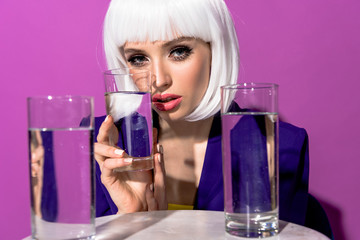 Stylish woman in white wig holding glass of water on purple background