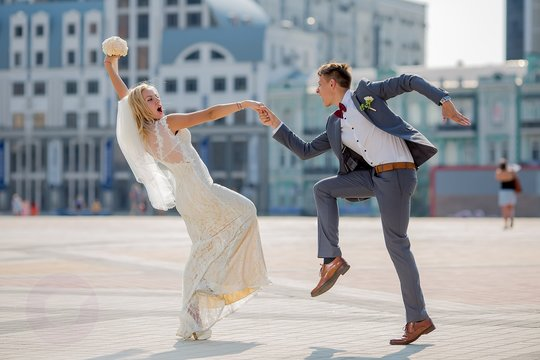 bride and groom in wedding attire dancing fiery dance in the town square