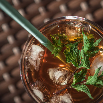 summer cocktail, brown in glass, ices, cold whisky, cold tea, cold coffee, green fresh plant
