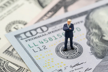 Miniature businessman leader standing and thinking on US Federal Reserve emblem on US dollars banknote as FED consider interest rate hike, economics and inflation control Wall mural