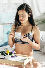 beautiful brunette woman in underwear holding cup while sitting near wooden tray with breakfast