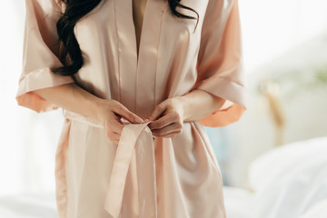 cropped view of woman untying silk robe at home
