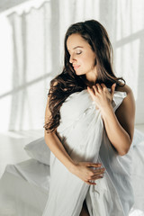 sensual brunette naked woman wrapped in blanket standing with closed eyes