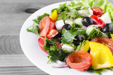 Vegetable salad cucumber capsicum tomato and olives on a white plate genuine black and white background