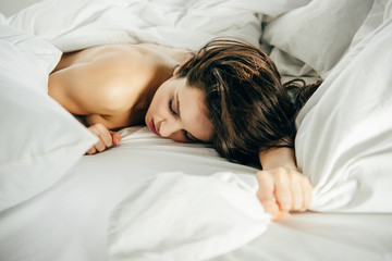 selective focus of naked brunette girl lying on bed with closed eyes