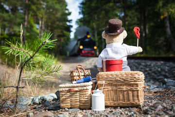 Start of Journey by Steam Railroad / Nostalgic teddy bear with big luggage waiting at railway track for approaching steam train, waving red signal flag
