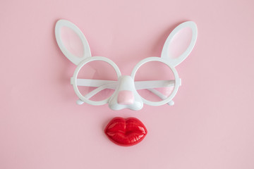 Flat lay of rabbit eyeglasses with plastic lips easter abstract.