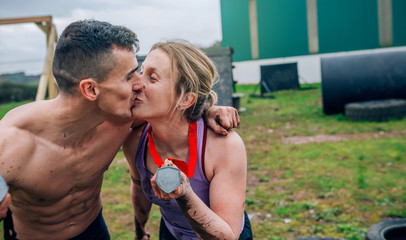 Athletes kissing and showing medals