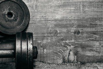 Fitness health workout gym equipment. Dumbbell or barbell on a wooden floor surface. Flat lay black and white concept picture