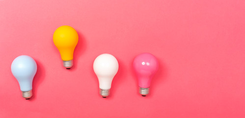 Wall Mural - Colored light bulbs on a pink paper background
