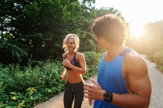 Cute sporty couple running in nature on the sunny summer day. Selective focus on woman.