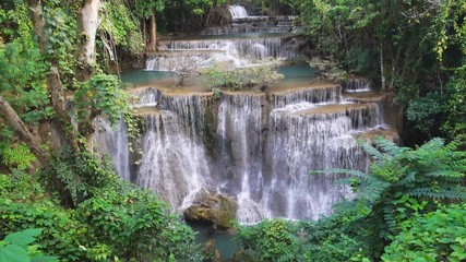 Wall Mural - Waterfall flow standing with forest enviroment high angle view in thailand called Huay or Huai mae khamin in Kanchanaburi Provience, Thailand., tilt up.