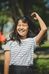 cheerful tan skin of asian teenager laughing in park