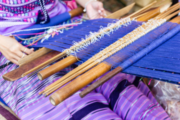 Thai Old women are using the machine - Household Loom weaving is Household occupation - for homemade silk or textile production of Thailand