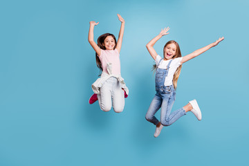 Full length body size view of two people nice lovely attractive charming cheerful careless glad straight-haired pre-teen girls having fun party overjoy cool day isolated on blue pastel background