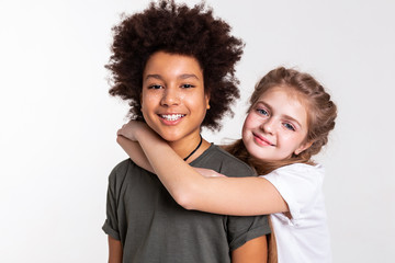 Smiling light-haired girl hanging on her African American boy