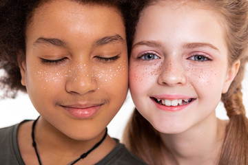 Appealing flawless kids connecting cheeks and displaying their faces