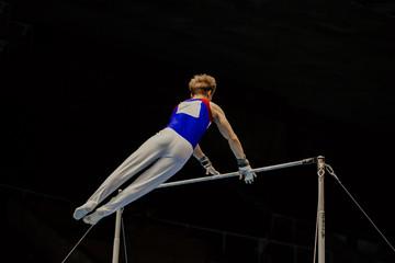 Fotobehang Gymnastiek male gymnast in artistic gymnastics exercise high bar