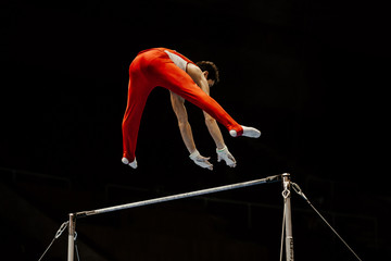 male gymnast exercise on high bar in black background