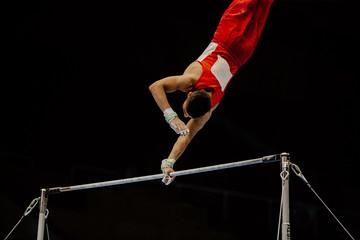 Fotobehang Gymnastiek exercise high bar athlete gymnast on black background