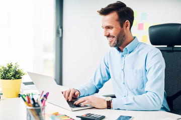 Happy man working on laptop at corporate office