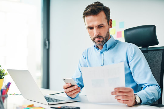 A man sitting at the desk at the office, checking financial documents and holding smartphone