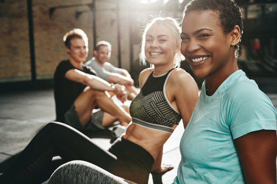Two laughing young women sitting together at the gym